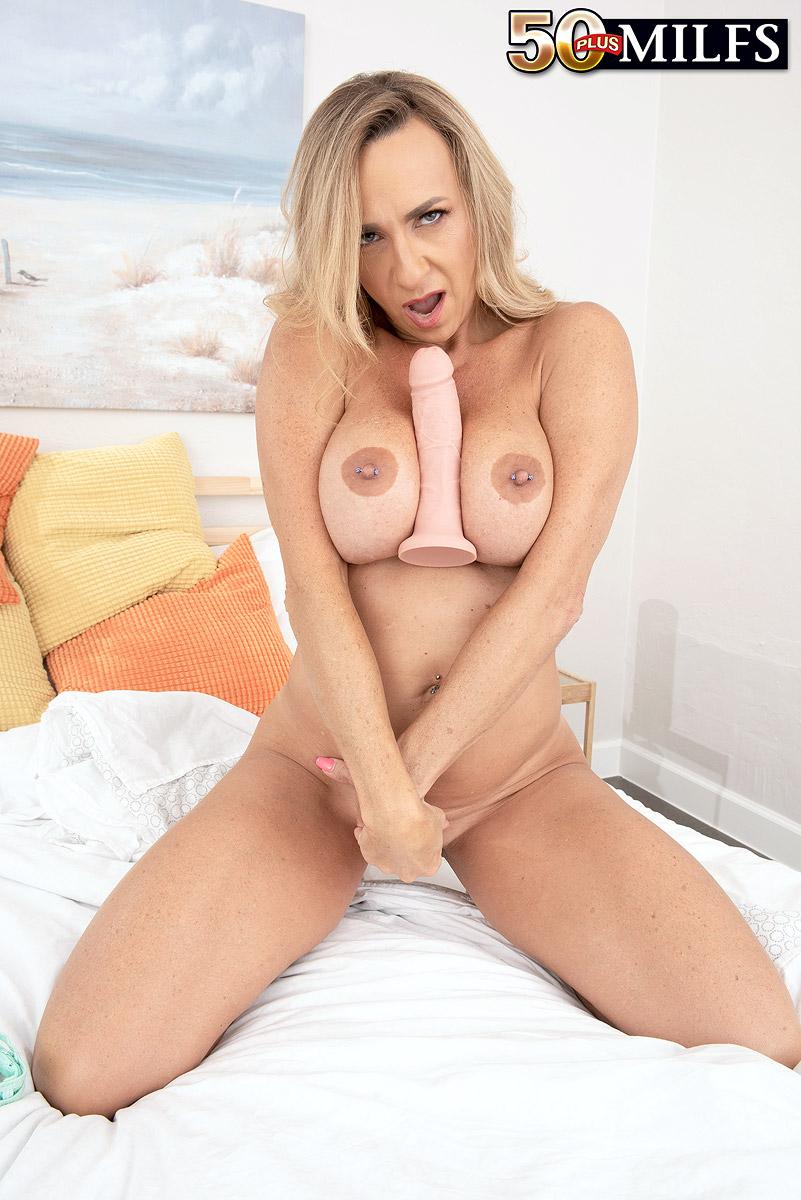 Big-titted elderly blonde Kenzi Foxx tweaks her nipples before masturbating with a fake penis