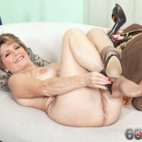 Solo GILF Bea Cummins stretches her shaven cunny after discarding biz attire and glasses