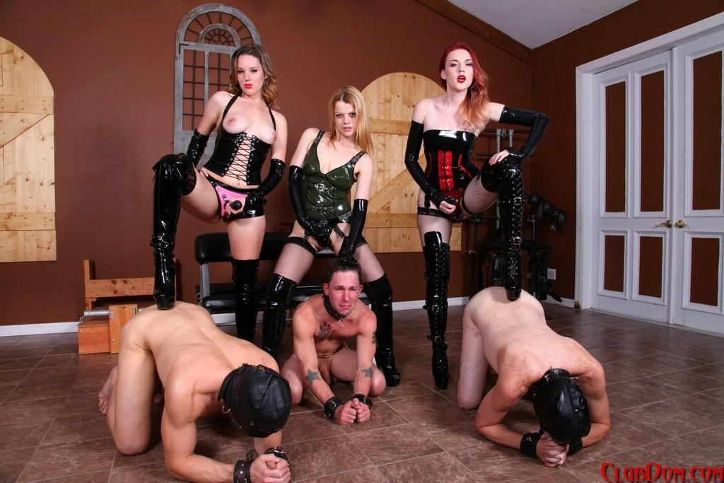 Dominatrixes anhandle male slaves with strap-on rods while garmente in latex clothing and boots