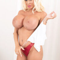 Hot platinum-blonde Barbie Nicole sets her enhanced titties loose during a solo shoot
