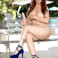 Big-titted elderly redhead Syren De Mer goes nude on a poolside patio in heels