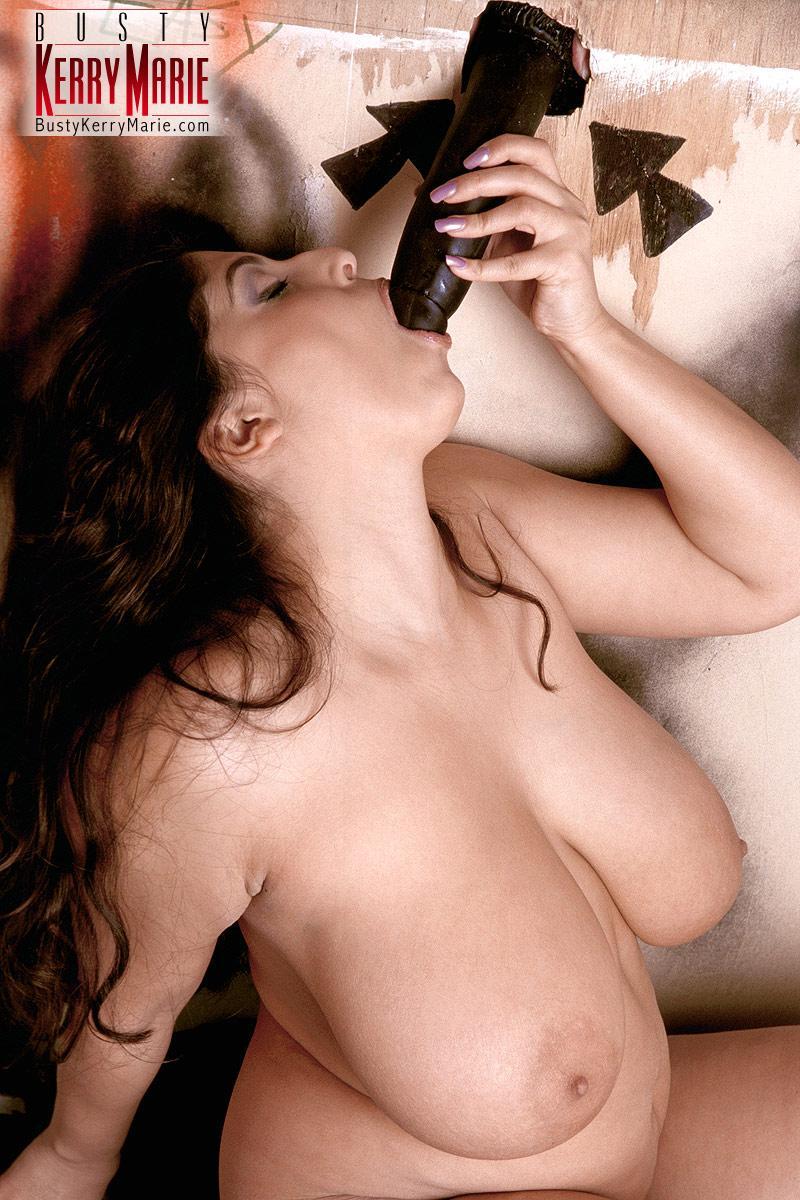 Big-boobed brunette plumper Kerry Marie fellates a cock via a gloryhole in wall