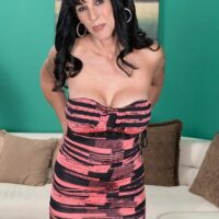 Dark haired MILF over fifty Moreen Helm exposing her monster-sized boobies for a younger guy in stockings
