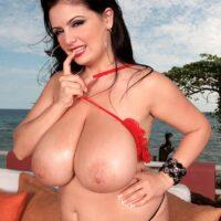 Dark haired MILF Arianna Sinn sets her hefty titties free of her revealing bra