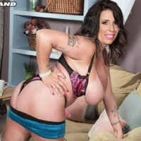 Inked black-haired MILF Amaya May frees her immense boobs from a brassiere in a mini-skirt