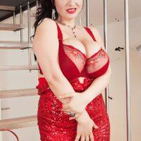 Dark haired model Joana Bliss sets her great breasts free of a short crimson dress in crimson stilettos