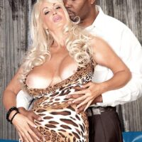 Lumbering blond MILF Brittany O'Neil whips out her immense boobs for an ebony boy on leather sofa