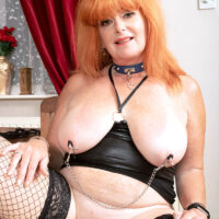 Huge-boobed mature redhead Melanie Taylor sports nipple clips while paddling her hefty bootie