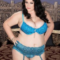 Dark haired fatty Charlotte Angel sets her immense boobs free of lingerie on top of a bed