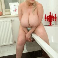 Big blonde woman Samantha Sanders frees her huge tits as she prepares for a bath