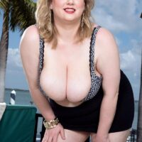 Over weight platinum-blonde chick Laddie Lynn displays her upskirt underwear along with her ample cleavage