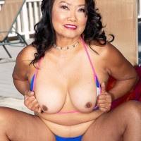 60 Plus Oriental MILF Mandy Thai peels off a string bathing suit to get naked by a pool