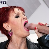 60 plus ginger-haired Caroline Hamsel entices a duo of men on the street in slutwear