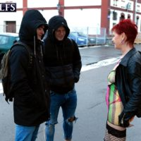 Sixty plus ginger-haired Caroline Hamsel seduces a couple of boys on the street in slutwear