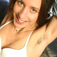 Amateur solo female stretches her all natural slit while modeling on a ebony leather couch