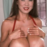Asian MILF XXX flick star Minka unsheathing enormous titties from crimson dress in high heeled shoes