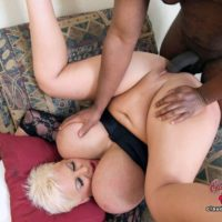 Giant titted platinum blond Claudia Marie participates in interracial sex on a chesterfield