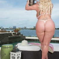 Blond BIG HOT WOMAN Holly Wood struts about in a thong bathing suit next to the ocean