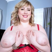 Ash-blonde BIG SEXY WOMAN solo model Laddie Lynn letting enormous floppy hooters loose from lingerie