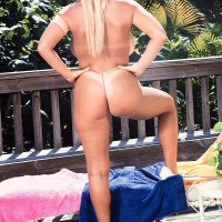 Golden-haired chick Honey Moons demonstrates her tan lined melons on the patio in pumps