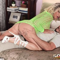 Sandy-haired cougar Brandi Jaimes tempts a guy in a semi-transparent fishnet dress and high heeled shoes