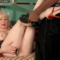 Golden-haired granny Jennifer Janes has her titties pawed while being stripped by a ebony stud