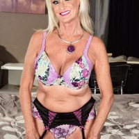 Platinum-blonde grannie Leah L'Amour gives her man toy a hand-job in lingerie and nylons