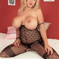 Yellow-haired model Dolly Fox sets her enhanced boobies loose of fabulous bodystocking in high heeled shoes