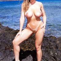 Blond solo female Danni Ashe rocks her great boobies while nude as the surf comes in