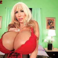 Fair-haired solo model Elizabeth Starr demonstrates her monster tits in a red brassiere