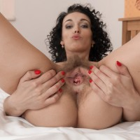 Black-haired amateur Cleo Fantasy unsheathing magnificent gams from stockings before spreading vagina