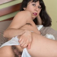 Black-haired amateur Vivi Marie stretches her full bush on a bed in frilly white socks