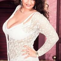 Dark-haired chick Lisa Miller sets her huge juggs loose on her bed in milky panties