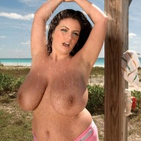 Dark-haired MILF Arianna Sinn flaunts her humungous breasts in the outdoors with the ocean in look