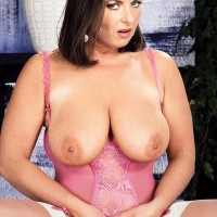 Black-haired MILF Effie sets her large boobs free of provocative lingerie in garters and stockings