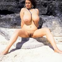 Brunette MILF Lisa Phillips touts her big boobs and butt on a sandy beach