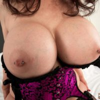 Dark-haired MILF over 50 Michaela O'Brilliant showcasing immense boobs before delivering BJ