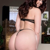 Brown-haired MILF Ryan Grins flaunting large butt in g-string underwear and high heeled shoes