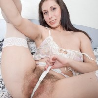 Brown-haired X-rated star Baby Boom pulling out fur covered twat from white underwear in pantyhose