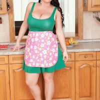 Brunette solo female Juliana Simms letting monster-sized tits loose from sundress in kitchen