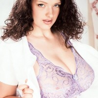 Brown-haired solo female Olga unveils her unshaven snatch after whipping out her big knockers