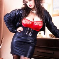 Brown-haired solo model Jeannine Oldfield lets out her gigantic juggs in leather and hosiery