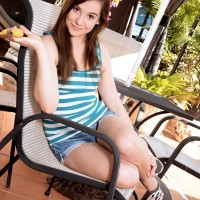 Black-haired nubile Kasey Warner eats a banana before unveiling her little tits outdoors