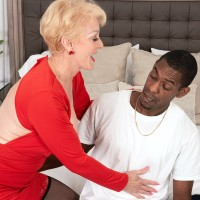 Busty blond grandma Seka Ebony holds a Voyeurism Tom's monster-sized black dick in her hand