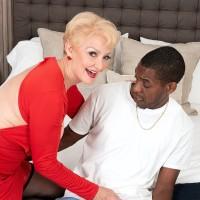 Busty blond grandma Seka Ebony holds a Voyeurism Tom's monster-sized black dick in her hand