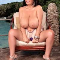Buxom brunette MILF Arianna Sinn pinching and licking her own nips outdoors