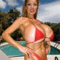 Huge-chested Chinese doll Minka models a pair bathing suits outdoors in close intimity to a pool