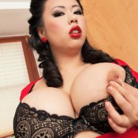 Asian MILF film star Tigerr Benson loosing her huge boobs from lingerie in a kitchen