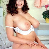 Round dark haired MILF Kerry Marie letting out massive natural boobies from milky boulder-holder