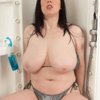 Plump MILF Emily Cartwright pinches her nipples after letting out fun bags from a swimsuit